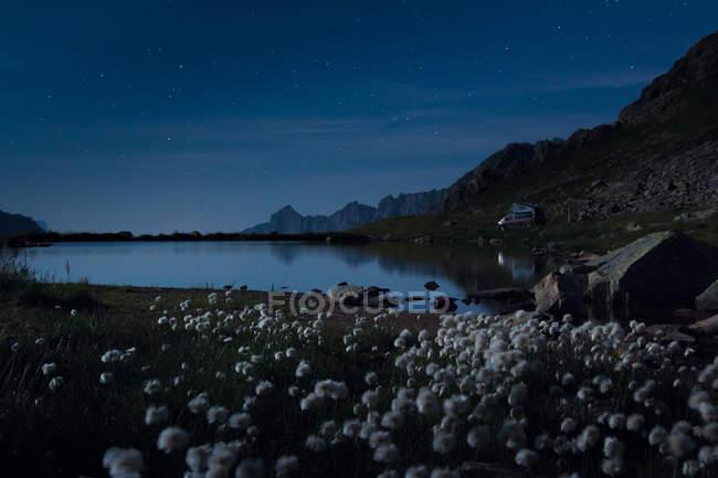 Pedras brancas na margem do lago com água cristalina refletindo céu e montanhas na Suíça — Fotografia de Stock