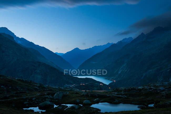 Misteriosa cordillera azul oscuro y río entre pendientes con luces a lo largo de la carretera en Suiza - foto de stock