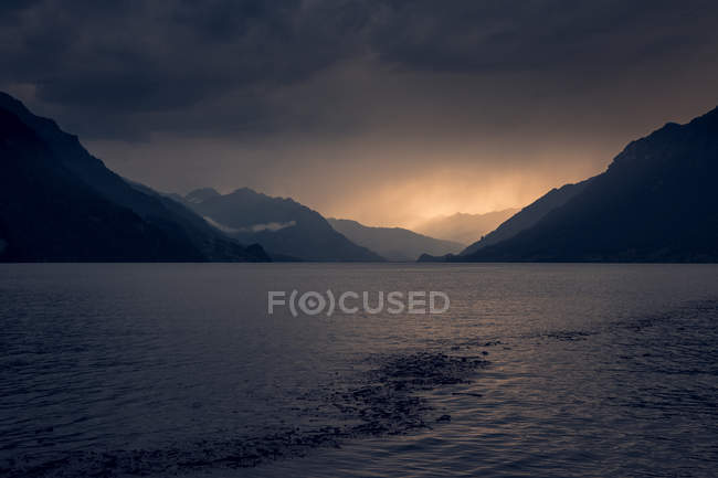 Calm landscape of dark rippled water under gray cloudy sky in mountains in Switzerland — Foto stock