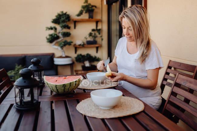 Беременная женщина в белой домашней одежде разрезает банан к белой миске на террасе — стоковое фото
