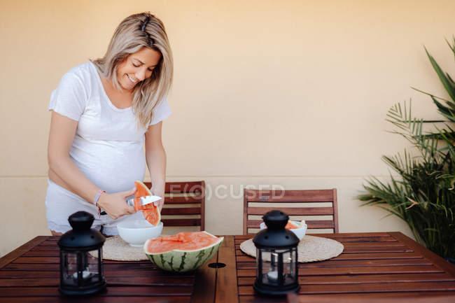 Беременная женщина в белой домашней одежде режет арбуз к белой миске на террасе — стоковое фото