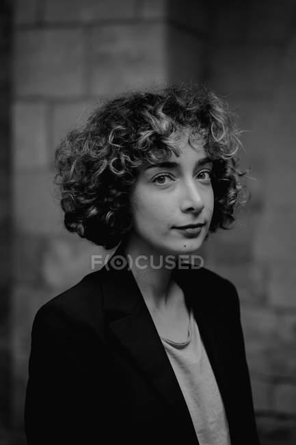 Mulher com cabelo encaracolado sorrindo e olhando para a câmera, enquanto em pé contra os passos na rua da cidade — Fotografia de Stock