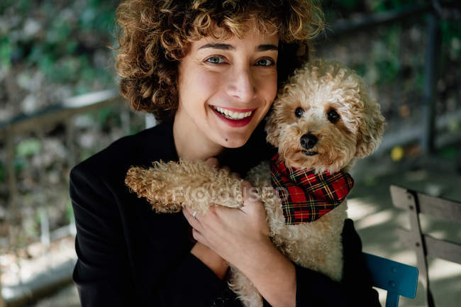 Delighted woman with curly hair hugging cute Toy Poodle and smiling for camera while resting on terrace — Stock Photo