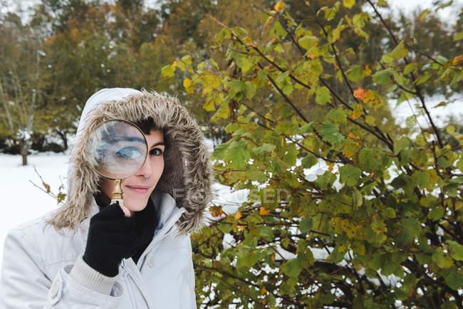 Женщина с пирсингом носа в белой зимней куртке с капюшоном на голове смотрит в камеру через увеличительное стекло — стоковое фото