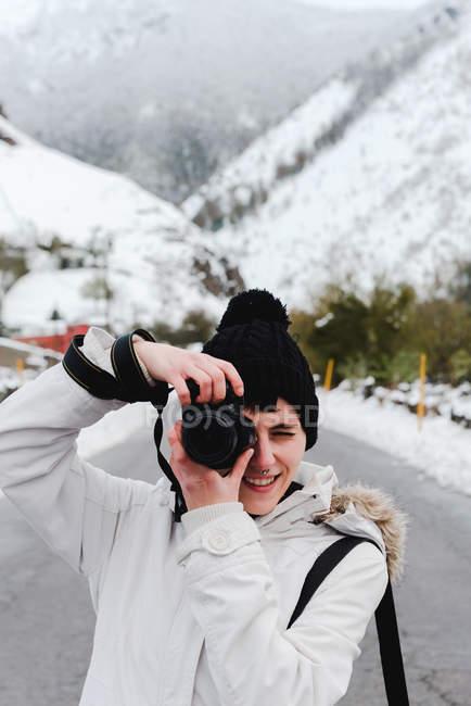 Donna in giacca bianca invernale con cappuccio e pantaloni neri scattare foto con macchina fotografica mentre in piedi in mezzo alla strada asfaltata — Foto stock