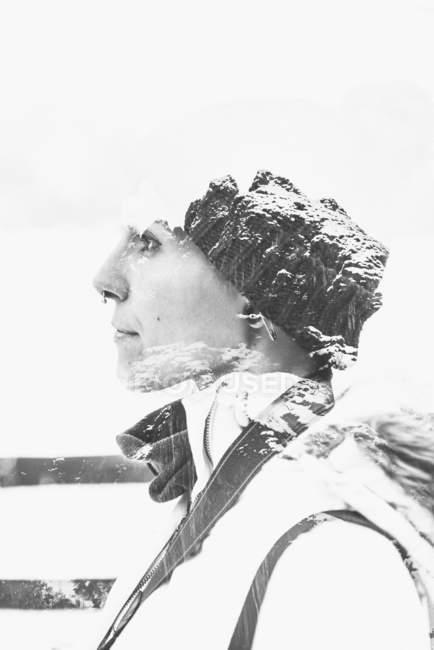 Doble exposición montañas en blanco y negro y retrato de mujer confiada en perfil con piercing en la nariz vestida con sombrero de invierno - foto de stock