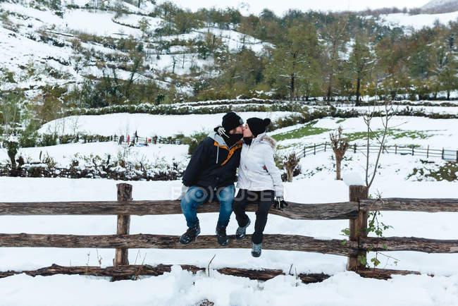 Homme et femme romantiques portant des vêtements d'hiver s'embrassant assis sur une petite clôture en bois sur la nature par temps neigeux — Photo de stock