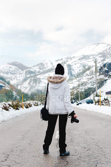 Back view of person in white winter jacket with hood on head standing in middle of asphalt road at foot of mountains at snowy weather — Stock Photo