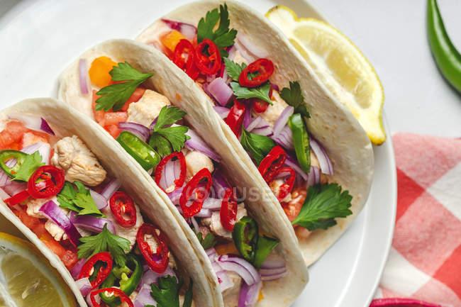 Hausgemachte mexikanische Tacos mit frischem Gemüse und Huhn auf weißem Hintergrund — Stockfoto