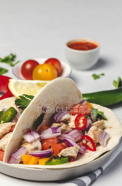 Tacos mexicanos caseros con verduras frescas y pollo de fondo blanco - foto de stock