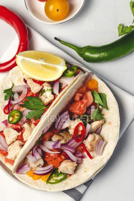 Домашний мексиканский такос со свежими овощами и курицей на белом фоне — стоковое фото