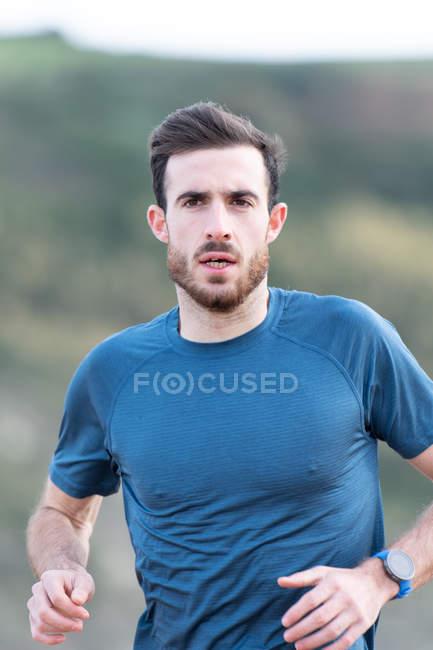 Atleta masculino barbudo em desgaste ativo correndo durante praia vazia de areia com montanhas verdes em fundo embaçado — Fotografia de Stock