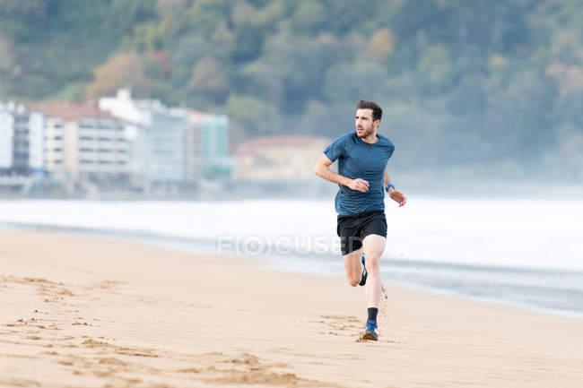 Одягнений чоловік у активний одяг, що бігає під час піщаного пляжу з зеленими горами на розмитому фоні. — стокове фото