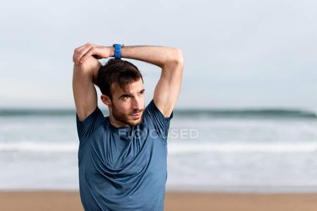 Одягнений у синю футболку, чоловік розтягує руки і дивиться з піщаним узбережжям на розмитому фоні — стокове фото