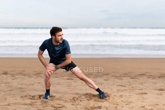 Male gymnast in sports clothing stretching legs and looking away on empty sandy beach with blue sea and sky on blurred background — Stock Photo