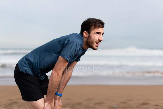 Вид сбоку босоногого спортивного мужчины в активной одежде, делающего перерыв после долгого пробега по песчаному пустырю и отводящего взгляд — стоковое фото