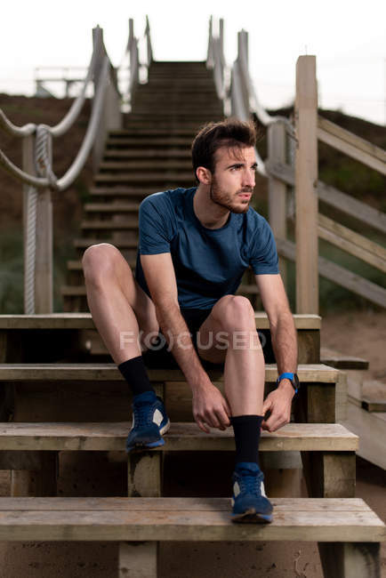 Бородатый мужской гимнаст в спортивной одежде сидит на деревянной лестнице во время подготовки к тренировке и смотрит в сторону — стоковое фото