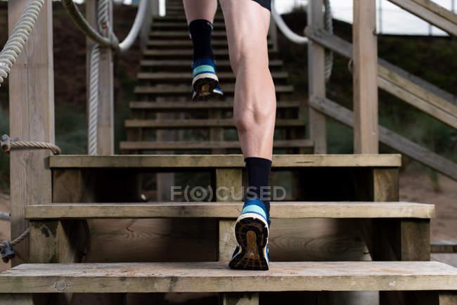 Знизу ви бачите атлета в спортивному одязі, який біжить нагору. — стокове фото