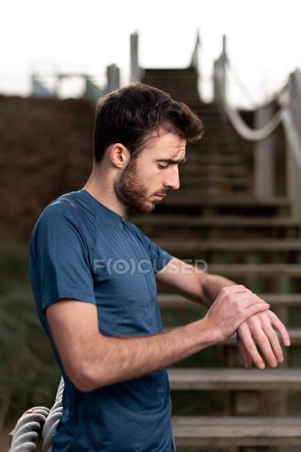 Вид сбоку бородатого мужчины в синей футболке, стоящего и проверяющего время на умных наручных часах — стоковое фото