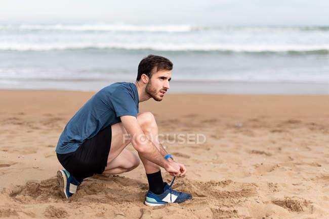 Боковой вид на бородатого спортсмена в активной одежде, сидящего на корточках и завязывающего шнурки на песчаном пустом побережье и отворачивающегося — стоковое фото