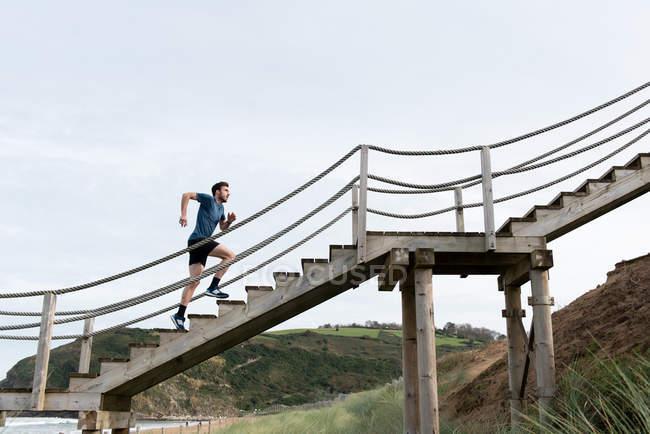 Вид снизу мужчины-спортсмена в спортивной одежде, бегущего вверх на фоне зеленых гор и неба — стоковое фото