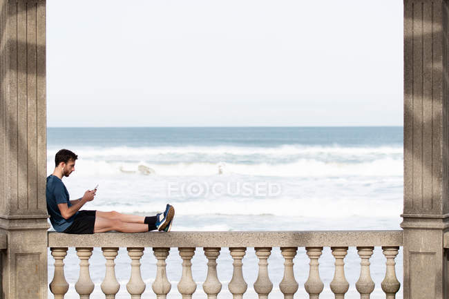 Вид сбоку человека в активной одежде, сидящего на раскачивающемся заборе и опирающегося на колонну при использовании мобильного телефона — стоковое фото