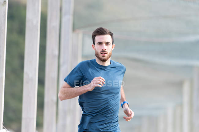 Highly motivated bearded male athlete in blue t shirt and shorts running outdoors under cover looking at camera — Stock Photo
