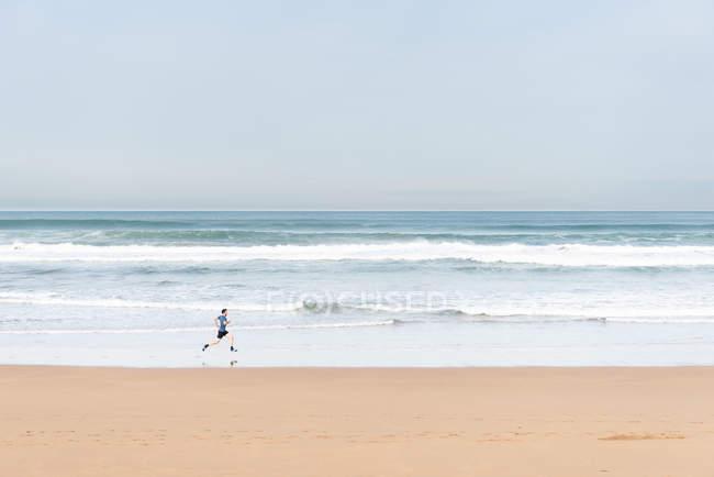 Бічний вид спортсмена в активному одязі, що бігає під час піщаного пляжу. — стокове фото