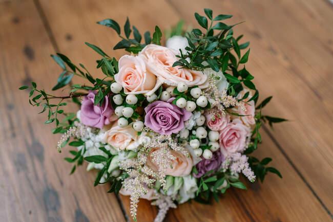 Beau bouquet de mariage délicat avec des fleurs roses et blanches et des plantes vertes décoratives sur une table en bois — Photo de stock