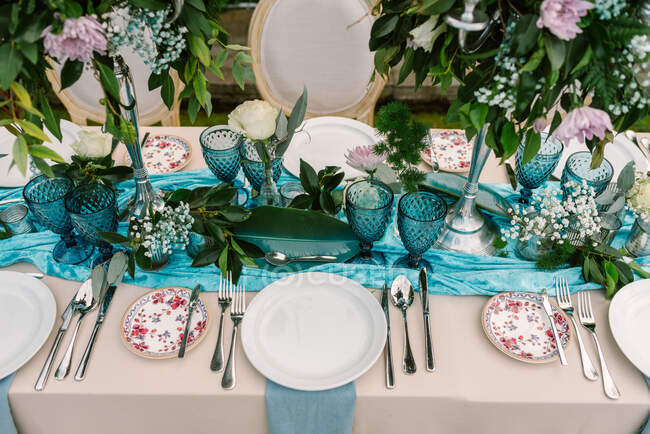 From above of wedding table decorated with blue and beige cloth and flowers bouquets in tall vases and served with porcelain plates and blue glasses — Stock Photo