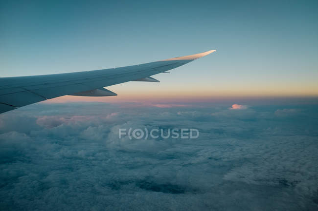 Вид с воздуха из окна самолета крыла над облаками в красивом вечернем небе с закатом света — стоковое фото