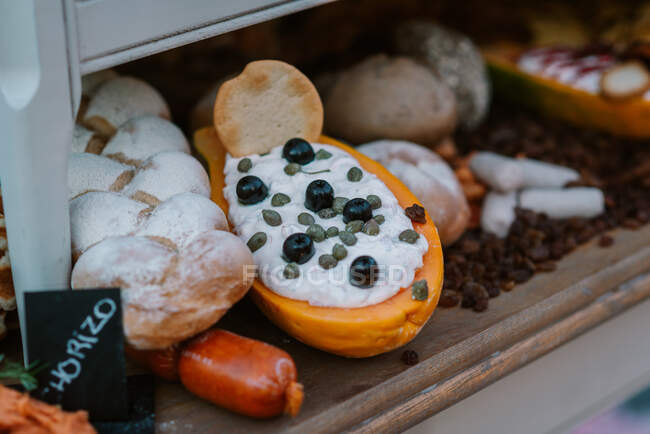 Ripe papaya fruit filled with white cream and decorated with berries next to breads and sausages placed on wooden counter — Stock Photo