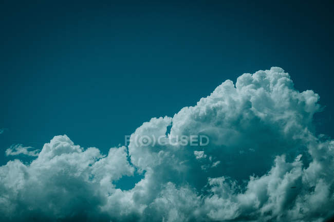 Aerial view from airplane window of white fluffy clouds and beautiful dark turquoise sky — Stock Photo