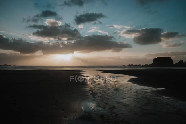 Bel coucher de soleil sur la mer avec ciel nuageux — Photo de stock