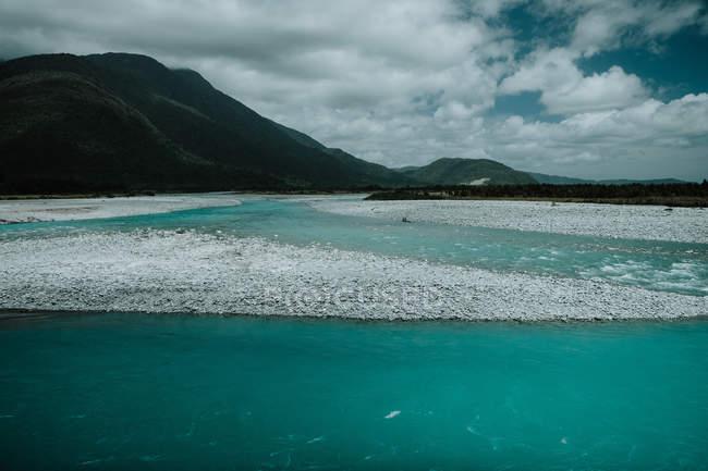 Новозеландське море з чудовою спокійною бірюзовою водою, оточеною зеленими пагорбами проти хмарного неба в літній день. — стокове фото