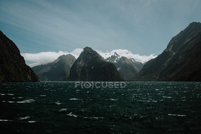 Majestosas montanhas escuras e lago tranquilo sob céu azul na Nova Zelândia — Fotografia de Stock