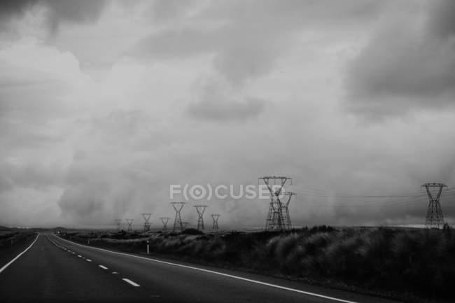 Nuvens tempestuosas sobre estradas pavimentadas vazias e postes de alta tensão no campo na Nova Zelândia — Fotografia de Stock