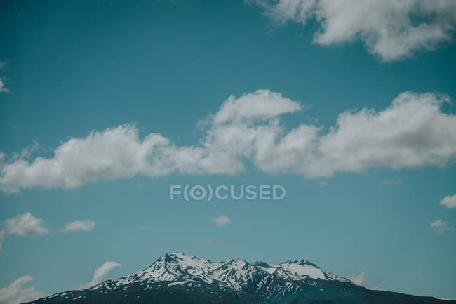 Mountains with snow on tops under blue sky with light clouds in New Zealand — Stock Photo