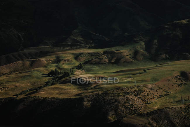 From above of green valley surrounded with dark hills at evening time in New Zealand — Stock Photo