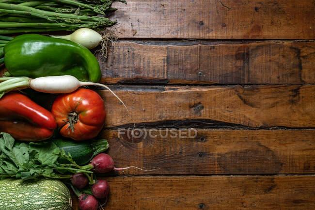 Verduras orgánicas frescas sobre una mesa de madera oscura - foto de stock