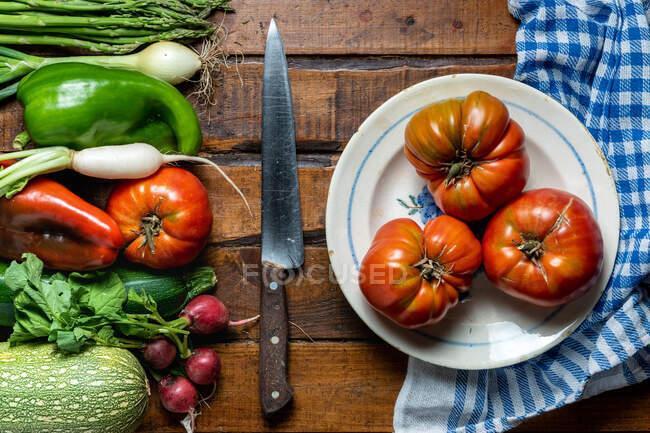 Legumes orgânicos frescos em uma mesa de madeira escura com tomates em uma tigela e uma faca — Fotografia de Stock