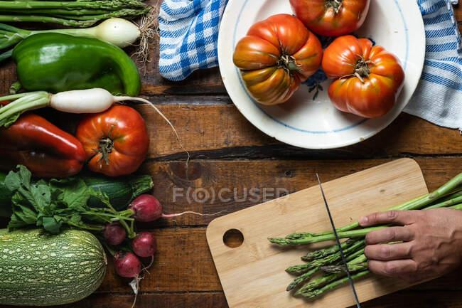 Vista superior de la persona de la cosecha cortando espárragos verdes en la tabla de cortar en tablón mesa de madera con tomates rojos maduros colocados en el plato blanco y verduras coloridas mixtas colocadas a un lado - foto de stock