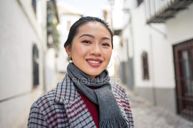 Touriste joyeuse en tenue décontractée sourire à la caméra dans la rue — Photo de stock