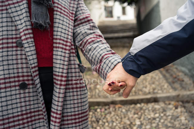 Casual anonymous couple holding hands and strolling in city — Stock Photo