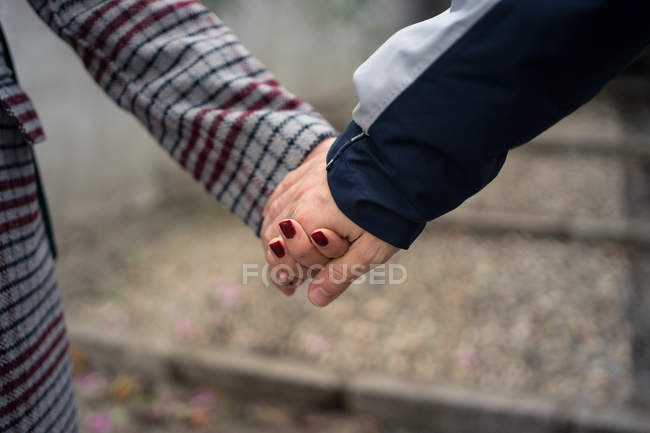 Close-up of casual couple holding hands and strolling in city — Stock Photo