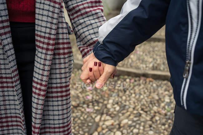 Dall'alto di anonimi amanti del maschio e della femmina in abbigliamento casual tenendo le mani mentre si cammina in città — Foto stock