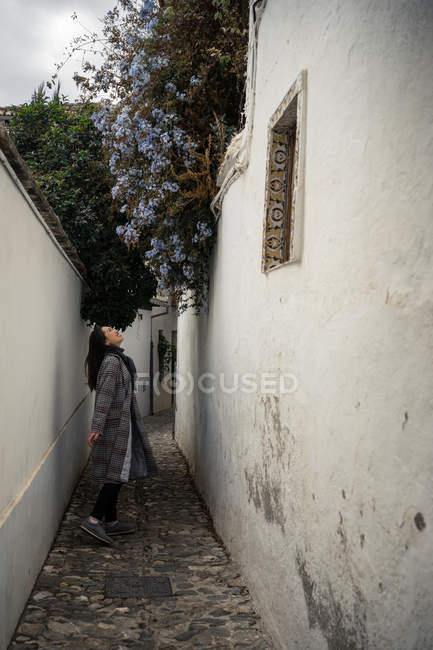 Joyful turista de uso ocasional en medio de estrechas calles de la ciudad. - foto de stock