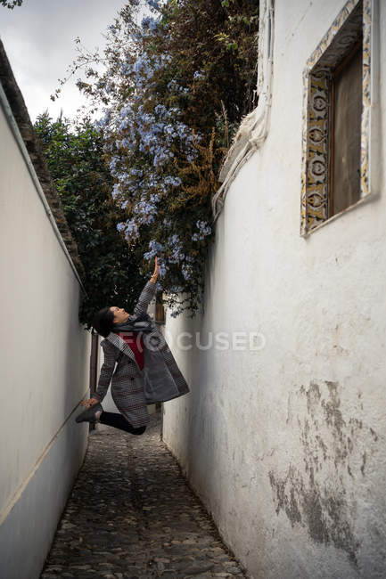 Joyful female tourist in casual wear jumping and touching flowers amid narrow city street — Stock Photo