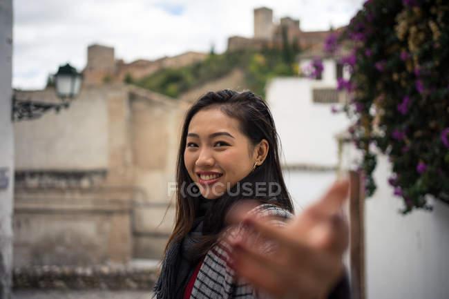 Las mujeres asiáticas que viajan en trajes cálidos sonreían entre los edificios antiguos cerca de un gran castillo. - foto de stock