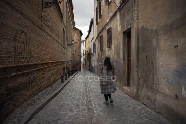 Mujer que camina por un antiguo callejón vacío con edificios antiguos. - foto de stock